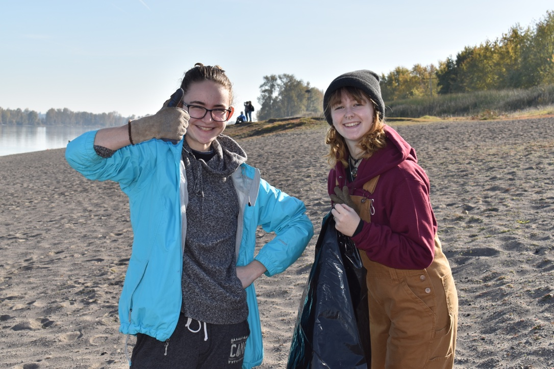 Sophomores Hayley Guy and Peyton Spencer collect trash at Walton Beach on Sauvie Island in a partnership with SOLVE.