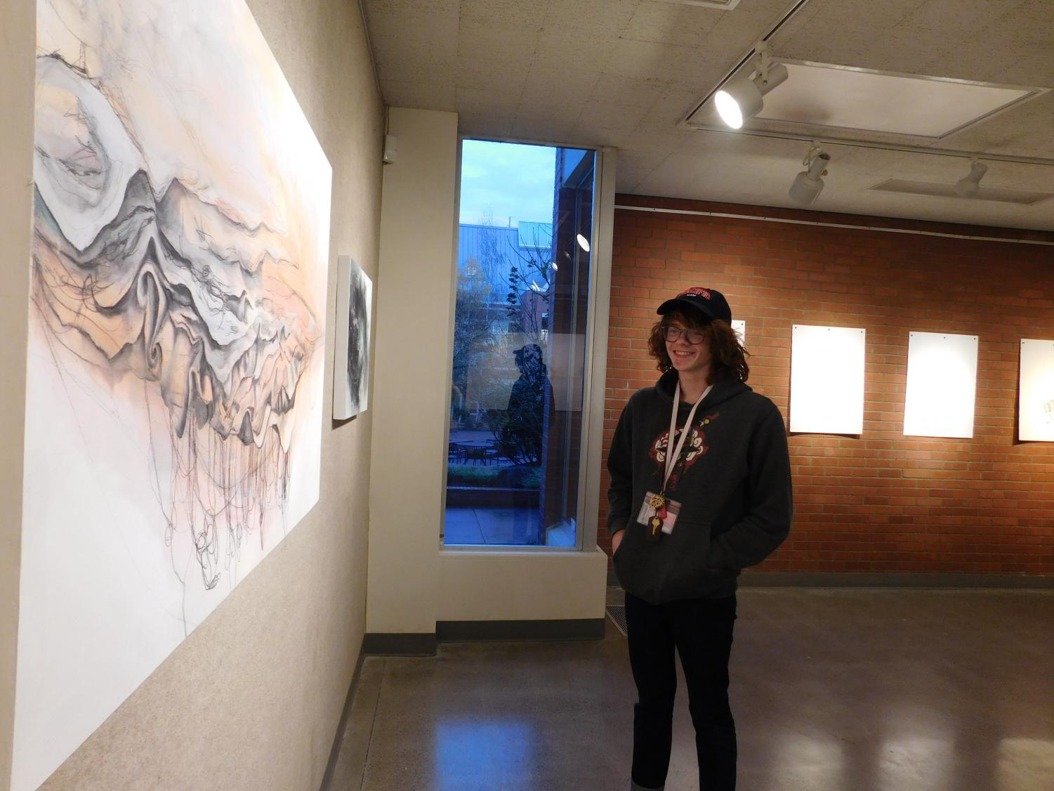 Student Seamus McCune observes Kate Lund's pieces from