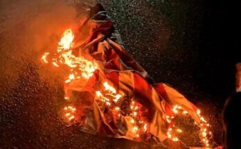 An American flag burns on the street of a Portland protest